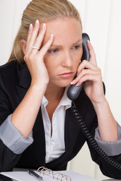 frustrated woman with phone in office